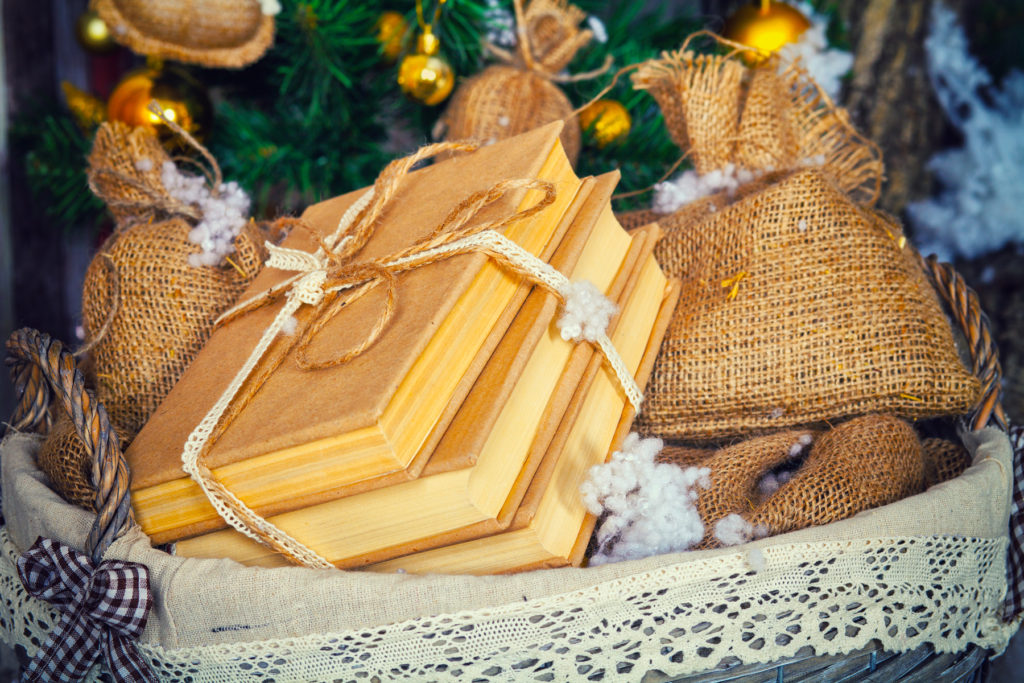 Stack of books and other presents in basket. Christmas decoratio